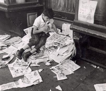 Niño leyendo tiras cómicas en una calle de Nueva York, de André Kertész
